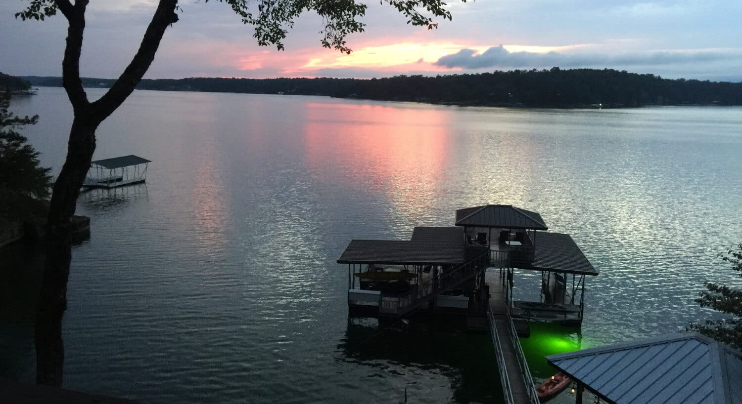 View of lake and underwater light next to a pontoon boat at evening.