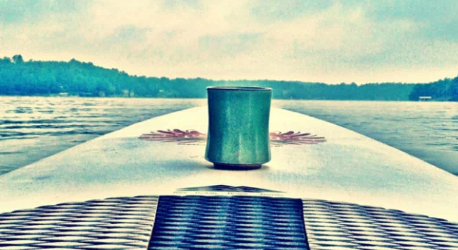 A blue coffee cup rests on the front of a paddleboard