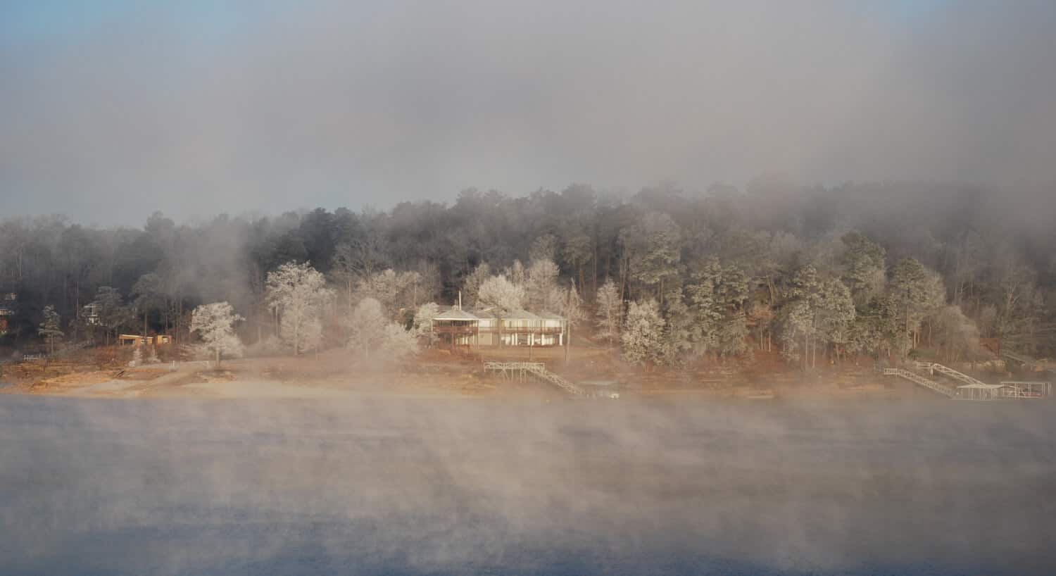 View of Smith Lake Bed & Breakfast through the early morning mist from the lake in the wintertime.