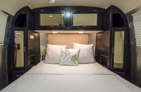 Large bed with white bedding in a classic Airstream trailer.