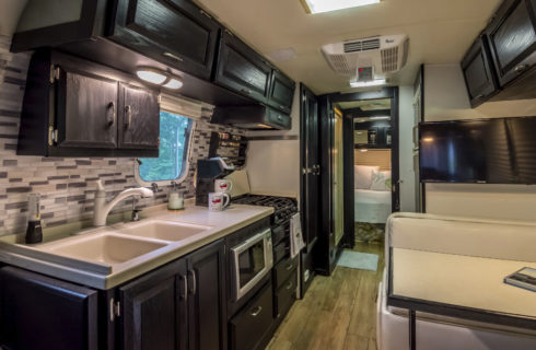 Galley kitchen in Airstream trailer with oven, stove, sink., fridge and microwave and dark wood cabinets.