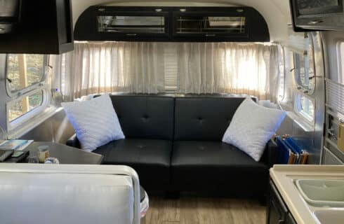 Black leather couch with white pillows between windows. Kitcheneete with bench seating.