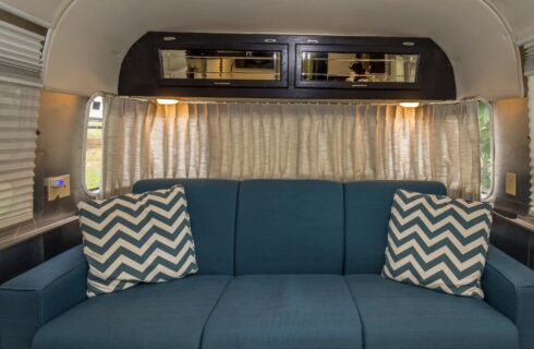 Brass daybed with travel-themed cover in the back of an antique Airstream trailer.