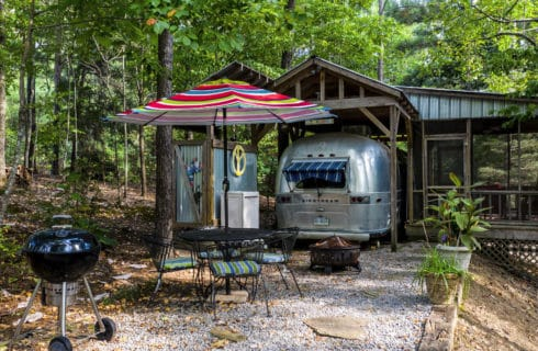 Vintage Airstream trailer parked under an awning in front of a table with a rainbow umbrella and chairs.