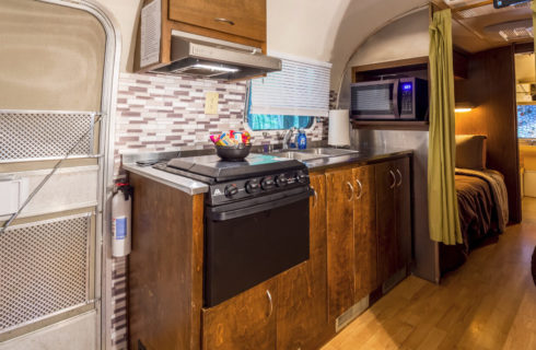 Airstream trailer kitchenw ith wooden cabinets, sink and stove/oven.