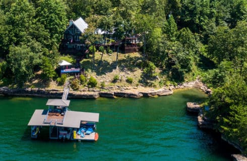 Overhead view of house and pier out to dock deck on a lake ringed by tree-lined shore.