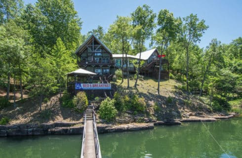 Large wooden building with pithced roof and longpier to lake with a sign: Smith Lake Bed & Breakfast