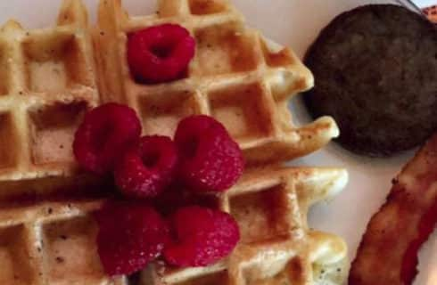 Waffles topped with raspberries next to sausage and bacon.