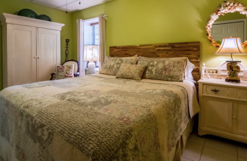Large bedroom with green walls and a bed made up in a cozy quilt.
