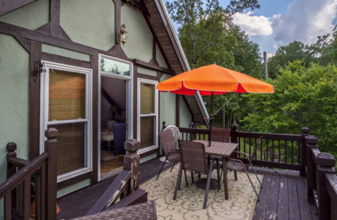Porch deck of green house with orange umbrella table and wooden railing.