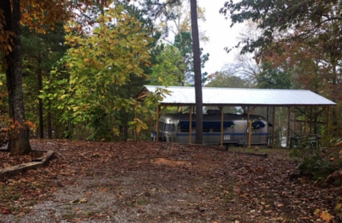 Open space in wooded area adjacent to a trauler under an awning.