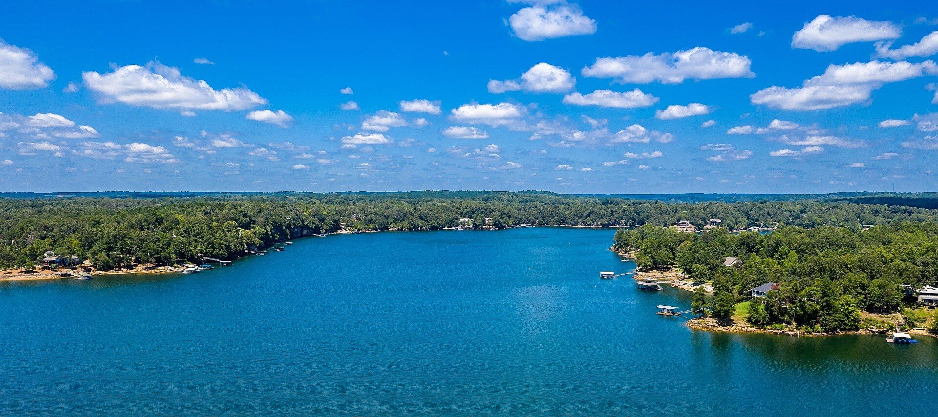 Panoramic view of large clear blue lake with houses and docks on the edge against a backdrop of blue sky and some white clouds