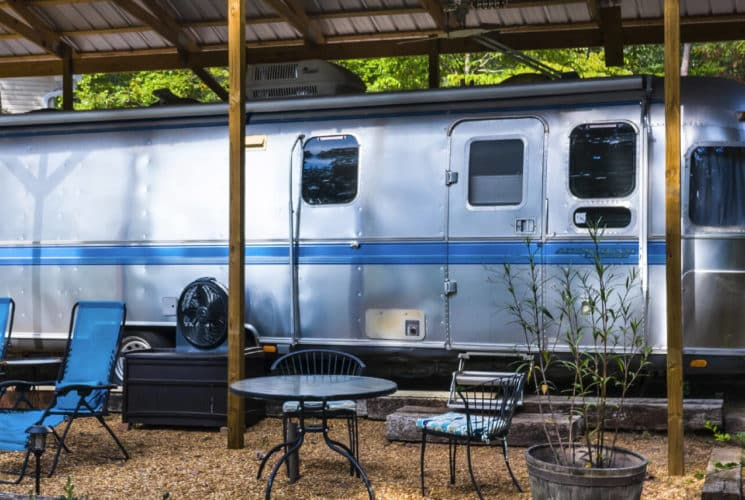 Vintage Airstream trailer parked under an awning with a patio containing chairs and a table.