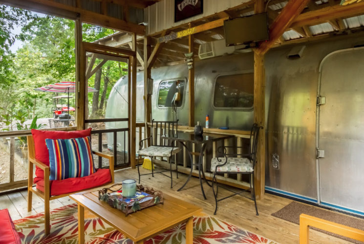 Wooden deck with railing next to an Airstream trailer equipped with tables and cahirs for lounging.