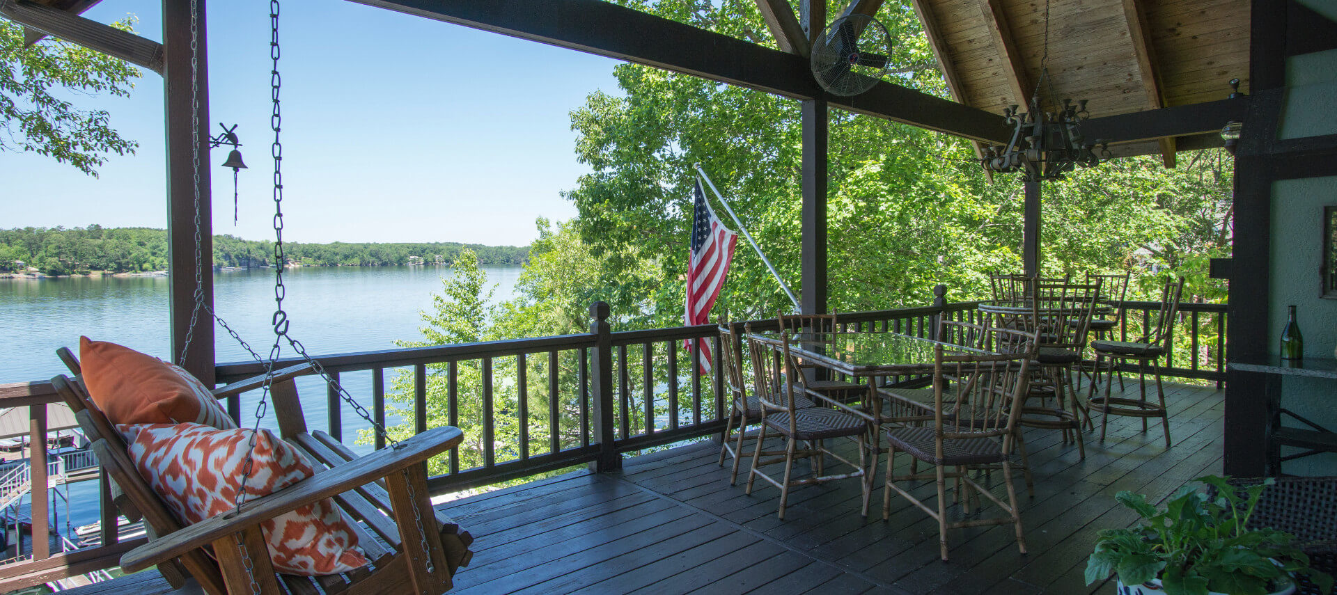 View of lake from deck with wooden tables and a rafter ceiling roof.
