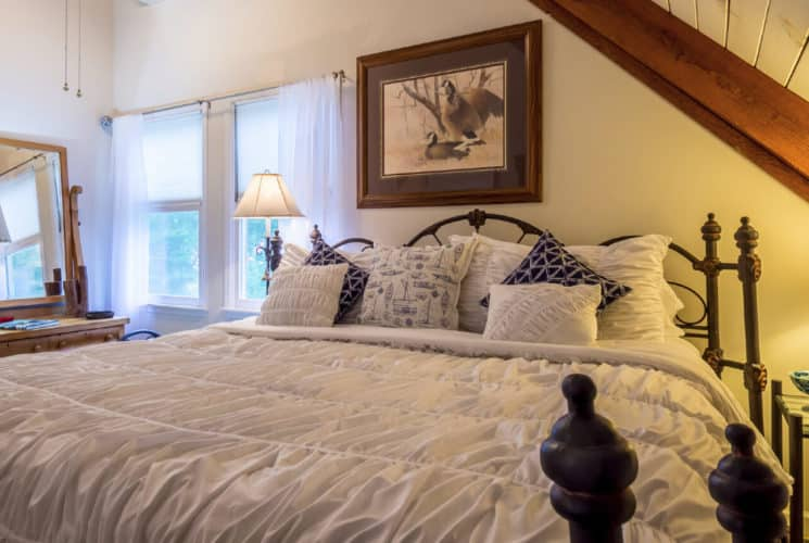 Large iron frame bed with comfortable soft bedding in a room with large windows and a pitched roof.