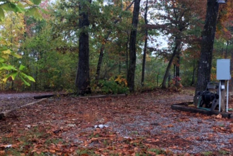Space for RV parking in wooded area with hookups.